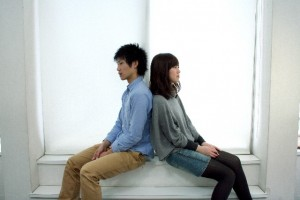 背中を合わせて座るカップル